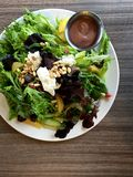 Green salad with goat cheese, pine nuts and balsamic dressing. A red and green lettuce salad served on a white plate. The salad is topped with chunks of chevre ( Royalty Free Stock Image