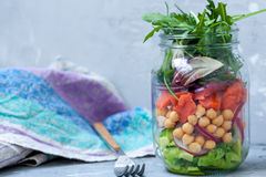 Green salad with layers of salmon, avocado and chickpeas in the jar Stock Images