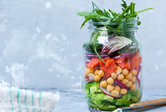 Green salad with layers of salmon, avocado and chickpeas in the jar Stock Photos
