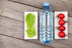 Green salad leaves, water bottle and tomatoes Stock Photography