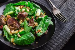 Green salad with liver and spinach on dark rustic background. Stock Photo