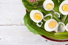 Green salad with onions and eggs on the white wooden table Stock Photo