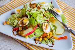 Green salad with quail eggs, corn and sweet apple Stock Image