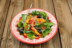 Green salad with raw vegetables: spinach, tomatoes, olives, onio Stock Images
