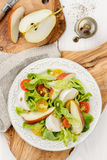 Green salad with red and yellow tomatoes, mozzarella, pear and p Royalty Free Stock Photos