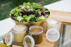 Green salad served in a bowl on a wooden table with three different dressings. Green salad served in a metal bowl placed on a wooden table with three different stock photography