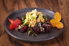Green salad with strawberry, blackberry, blood oranges, alligator pear, beets, seeds and nuts on a wooden background,. Selective focus, free space. Delicious royalty free stock photos