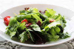 Green salad with strawberry pieces and a dressing of orange juice royalty free stock photo