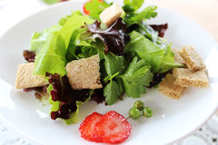 Green salad with strawberry pieces. And a dressing of orange juice stock images