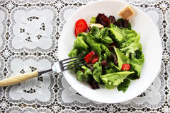 Green salad with strawberry pieces. And a dressing of orange juice royalty free stock photography