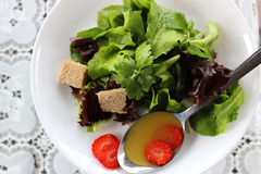 Green salad with strawberry pieces. And a dressing of orange juice royalty free stock photo