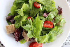 Green salad with strawberry pieces. And a dressing of orange juice stock photo