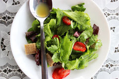 Green salad with strawberry pieces. And a dressing of orange juice stock image