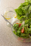 Green salad, tomatoes and olives in glass bowl and water with le Stock Photo