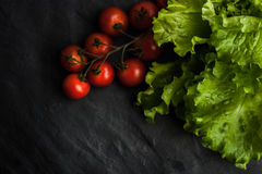 Green salad  and tomatoes twig one the black stone table Royalty Free Stock Photos