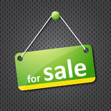 Green for sale sign. Hung on grey texture Stock Images
