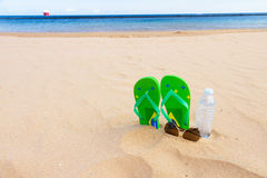 Green sandals on sandy beach Royalty Free Stock Photo