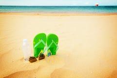 Green sandals on sandy beach Stock Photography