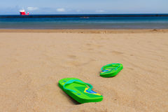 Green sandals on sandy beach Royalty Free Stock Photography