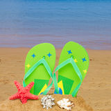 Green sandals and starfish in sand Stock Photos