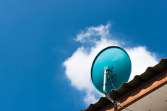 Green Satellite dish on the roof with a beautiful blue sky. stock photo