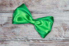 Green Satin bow tie on wooden background. St. Patricks Day Royalty Free Stock Photography