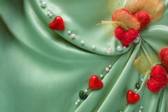 Green satin cloth with hearts and empty space. Green satin cloth with red hearts and empty space Stock Photo