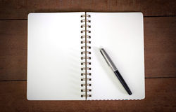 A Pen on A Notebook with Wood in Background Royalty Free Stock Images