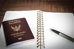 A Thailand Passport, A notebook, and A pen in A Wooden background. Stock Photo