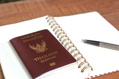 A Thailand Passport, A notebook, and A pen in A Wooden background. Royalty Free Stock Photos