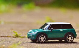 Green Scale Model Car on Brown Pavement Stock Images