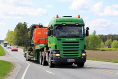 Green Scania Semi Truck Transports Excavator at Spring Stock Photo