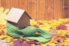 Green scarf around a miniature house on autumn leaves background. Concept of protecting or isolating house. Green scarf around a miniature house on the autumn royalty free stock photo