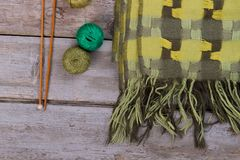 Green scarf with plaid pattern. Wooden needles and balls of cotton yarn. Knitting tools and handmade goods Royalty Free Stock Photo