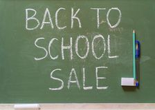 Green school board with the inscription sale surrounded by a variety of office. Inscription back to school sale on green school blackboard with chalk pen and stock photos