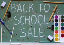 Green school board with the inscription sale surrounded by a variety of office royalty free stock images