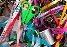 Green scissors on the bunch of ribbons Royalty Free Stock Photos