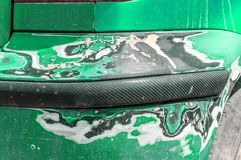 Green scratched car with damaged bumper paint and body in crash accident or parking lot royalty free stock photos