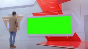Green screen concept - woman looking at blank large interactive wall display. Green screen, mock up, template, copyspace, chroma key concept. Woman looking at stock video