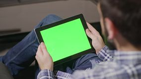 Green Screen Digital Tablet PC Man. Young man using digital tablet pc with blue screen sitting at home. Rear view stock video