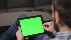 Green Screen Digital Tablet PC Man. Young man using digital tablet pc with blue screen sitting at home. sliding stock video footage