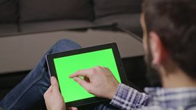 Green Screen Digital Tablet PC Man. Young man using digital tablet pc with blue screen sitting at home. sliding stock footage