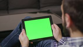 Green Screen Digital Tablet PC Man. Young man using digital tablet pc with blue screen sitting at home. tap stock footage