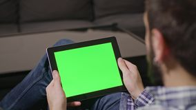 Green Screen Digital Tablet PC Man. Young man using digital tablet pc with blue screen sitting at home. zoom stock video