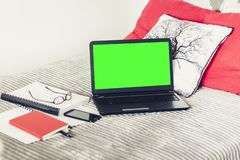 Green screen laptop, notebook, smartphone, glasses and pen on bad, education concept background.  stock photography