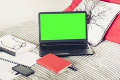 Green screen laptop, notebook, smartphone, glasses and pen on bad, education concept background.  stock photos