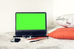 Green screen laptop, notebook, smartphone, glasses and pen on bad, education concept background.  royalty free stock image