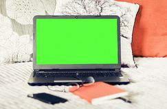 Green screen laptop, notebook, smartphone, glasses and pen on bad, education concept background.  royalty free stock images