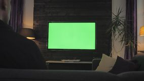 Green screen - man watching tv in the living room. Over the shoulder shoot.