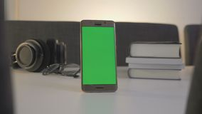 GREEN SCREEN mobile phone standing on the white table. Dolly movement stock video footage